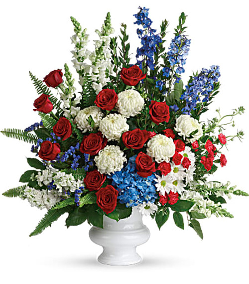 """Patriotic Funeral Flowers Arrangement by Enchanted Florist Pasadena TX. A patriotic mix of all-American red, white and blue flowers such as hydrangea, roses, miniature carnations, snapdragons, mums and more are perfectly arranged in a white urn. Approximately 31"""" W x 34"""" H SKU RM573"""