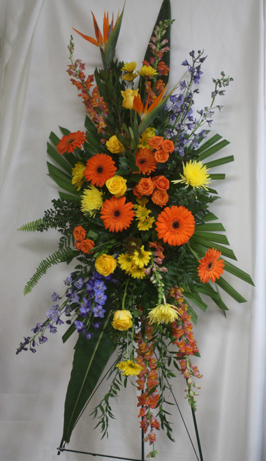 "Yellow Rose Autumn Funeral Spray of Flowers from Enchanted Florist. Our autumn sympathy arrangement of flowers includes orange gerbera daisies, birds of paradise, orange spray roses, yellow spiders, blue delphinium, orange snapdragons, and are accented with various greenery and arrives on a funeral easel. Approximately 70""H x 30""W  SKU RM515"