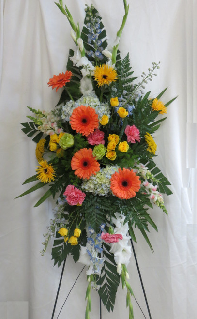 """Last Farewell Blue Hydrangea Funeral Spray from Enchanted Florist. This lovely funeral spray of flowers arrives on an easel and includes blue hydrangeas, orange gerbera daisies, yellow spray roses, yellow gerbera daisies, blue delphinium, white gladiolas and other flowers are designed with greenery. Approximately 70""""H x 30""""W SKU RM517"""