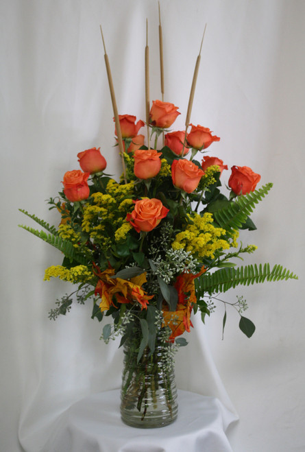 """Fall Orange Dozen Roses with Yellow Solidago from Enchanted Florist. Your fall fanatic will love this Autumn themed dozen roses, a traditional flower gift with a twist. This colorful standard roses includes the vibrant orange roses with contrasting yellow solidago filler, fall leaves and mini cattails to accent. Approximately 18""""W x 27""""H SKU RM211"""