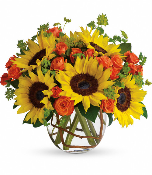 """Sunflowers and Orange Roses Fall Bouquet from Enchanted Florist. The sunflowers steal the show in this simple, yet beautiful arrangement. Also featured: mini orange spray roses, green bupleurum, salal leaves and a curly willow inside the glass bubble bowl. Approximately 12"""" W x 12"""" H SKU RM223"""
