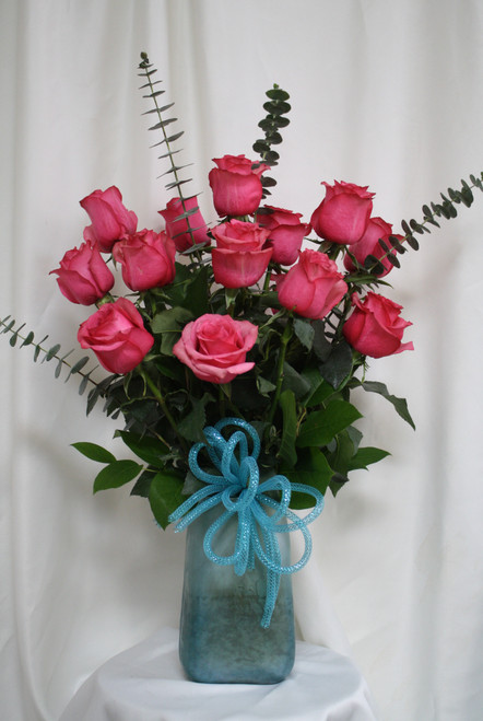"""Turquoise Vase with Hot Pink Rose Bouquet from Enchanted Florist. This beautiful bouquet of roses includes 15 premium pink roses arranged along side spiral eucalyptus, adorned with a turquoise bow and arrives in our beautiful exclusive turquoise art vase. Approximately 24""""H x 16""""W SKU RM357"""