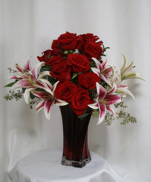 """Luxurious Love Red Rose and Stargazer Bouquet from Enchanted Florist. Our one of a kind bouquet includes the Red Luxurious keepsake vase and has 15 beautiful Ecuadorian red roses designed in it alongside fragrant stargazer lilies and seeded eucalyptus to accent this arrangement perfectly. Approximately 19""""H x 13""""W SKU RM359"""