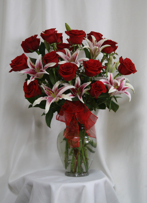 """Grand Love Stargazer and 15 Red Roses Bouquet from Enchanted Florist. Our beautiful and popular bouquet includes 15 beautiful Ecuadorian red roses designed in it alongside fragrant stargazer lilies and accented with a red sheer bow. Approximately 25""""H x 16""""W SKU RM362"""