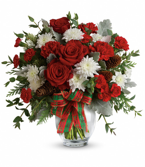 """Holiday Shine Bright Christmas Bouquet from Enchanted Florist. Our bold bouquet includes red carnations, red miniature carnations, white cushions, flat cedar, noble fir, eucalyptus, small pinecones and wired ribbon. Delivered in a glass ginger jar. Approximately 16"""" W x 16"""" H SKU 257"""