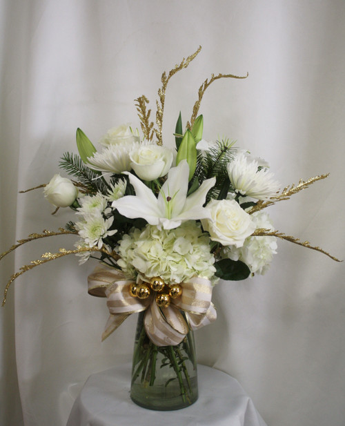 """Winter Wonder White and Gold Holiday Bouquet from Enchanted Florist. This unique and beautiful bouquet comes hand delivered with white roses, hydrangeas, oriental lilies, cremons, and cushions in a clear vase. It is accented with gold's and includes fresh, fragrant Christmas greenery to tickle the senses.  Approximately 20"""" W x 24"""" H   SKU RM263"""