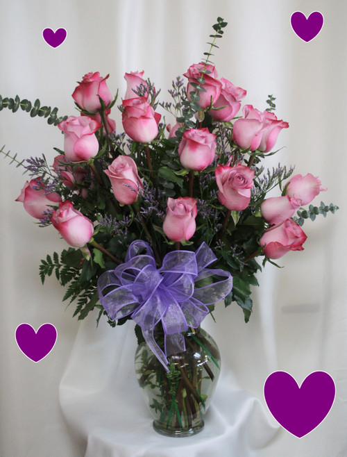 """Two Dozen Purple Roses for Valentine's Day by Enchanted Florist Pasadena TX. This show stopping bouquets of our lush and romantic purple roses comes complete with baby's breath, greens and a bow and is hand arranged by our premier floral designers. STANDARD Option in pictured with 24 purple roses. The Deluxe Option will have 27 purple roses and the Premium Option will have 30 purple roses.  Approximately 26""""H x 16""""W   SKU RM957"""