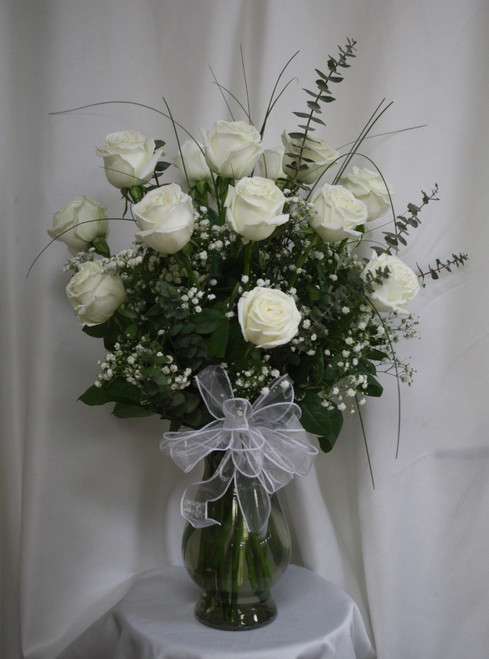 Classic One Dozen White Roses by Enchanted Florist. White roses are a classic and timeless choice when sending thoughts of love and compassion. The freshest premium white roses will be hand designed in our upgraded Bella vase, with popular baby's breath, upgraded premium greenery like bear grass and eucalyptus.  SKU RM377