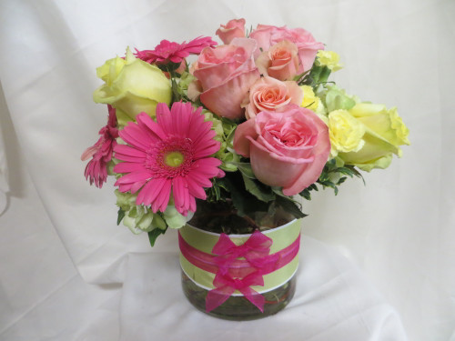 """Fun Fashionista Pink Rose Bouquet by Enchanted Florist Pasadena TX is a fun and flirty bouquet of pink roses, pink gerbera daisies, yellow roses and green hydrangeas in a contemporary cylinder with a fun ribbon treatment. A perfect gift for the flower lover in your life.  RM185 Approximately 9""""H x 9""""W"""