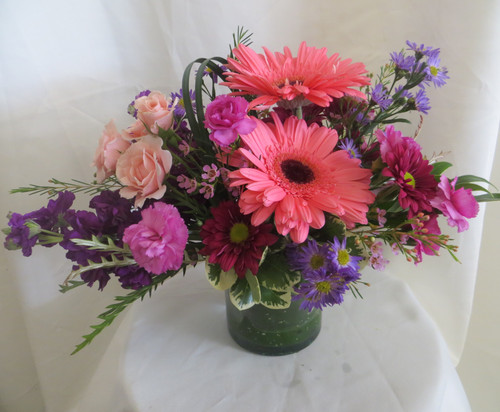 """Pink Moscato Gerbera Daisy Flower Bouquet from Enchanted Florist. This beautiful bouquet includes pink gerbera daisies, purple stock, light pink spray roses, pixie carnations and more and arrives in this clear glass vase with a leaf inside for some mystery and is hand designed by our expert floral designers. Approximately 12""""H a 12""""W. For local delivery only. SKU RM151"""