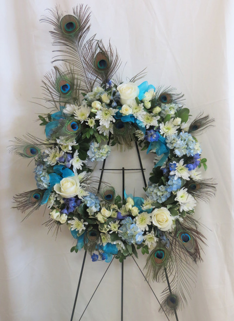"""Peacock Blue and White Funeral Wreath Flowers by Enchanted Florist Pasadena TX. The funeral wreath includes white roses, blue hydrangeas, white cushion mums, white spray roses, and blue delphinium designed on a wreath shaped spray and includes the wire easel. Approximately 32""""H x 26""""W.   SKU RM526"""