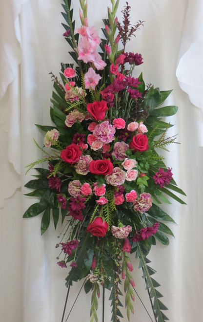 """Jeweled Hot Pink Rose Funeral Spray by Enchanted Florist Pasadena TX.  A pink mixed spray of sympathy flowers in a standing spray and includes pink carnations, hot pink roses, pink gladiolas, pink spray roses and more. A beautiful funeral flowers for a woman. Approximately 70""""H x 35""""W.   SKU RM546"""