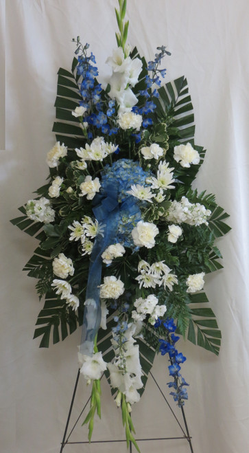 """Sapphire Blue & White Funeral Spray from Enchanted Florist.  Our beautiful blue and white sympathy standing spray of flowers.  It includes blue delphinium, blue hydrangeas, white carnations and white stock with accent foliages. Approximately 70""""H x 36""""W size not including stand. SKU RM547"""
