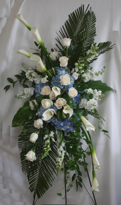 """Galaxy Wide Blue and White Funeral Flowers Spray from Enchanted Florist. One of our largest sprays in blue and whites, our custom spray includes large white calla lilies, one dozen white roses. blue hydrangeas, white stock, white snapdragons, and lots of green foliage to set the design off. Approximately 70""""H x 40""""W (size not including stand) SKU RM548"""