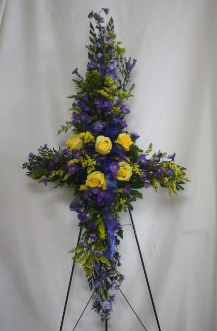 """Golden Cross with Purple Flowers by Enchanted Florist - sympathy cross of purple flowers will honor your loved one in an unique way during the service. One cross of yellow roses, blue delphinium, and purple novi belgi arrives on a wire easel stand with a sheer bow. Approximately 36"""" W x 50"""" H. (Dimensions don not include stand.)  SKU RM549"""