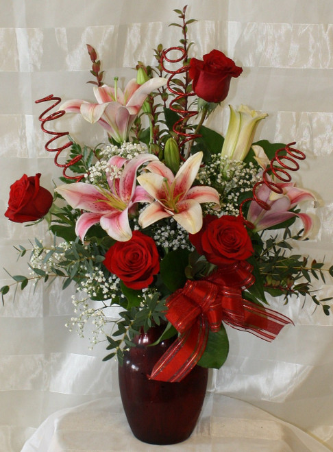 """My Heart Is Yours Red Roses and Stargazer Lilies from Enchanted Florist. This beautiful red bouquet includes fragrant stargazers lilies, classic red roses, and baby's breath for that traditional feel. Approximately 21""""H x 14""""W.  For local delivery only. SKU RM126"""