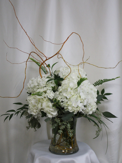 """The Chloe White Hydrangea and Greenery Bouquet from Enchanted Florist. This beautiful and simple arrangement includes all white hydrangeas in a clear vase that is accented with several types of classic greeneries and curly willow. Approximately 20""""H x 18""""W SKU RM131"""