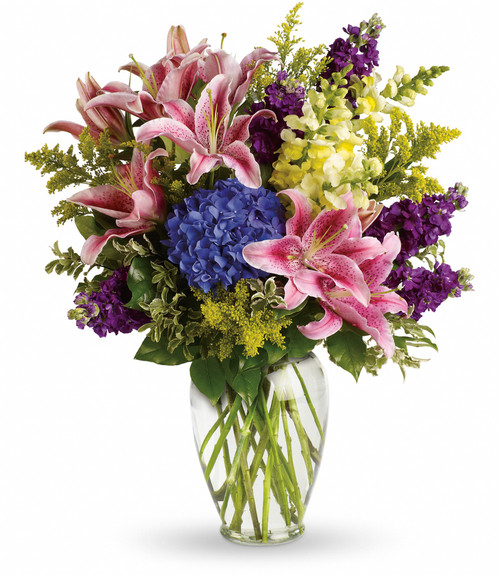 """Crush Everlasting Blue Hydrangea Bouquet from Enchanted Florist Pasadena TX. The stunning bouquet includes blue hydrangea, pink oriental lilies, yellow snapdragons and purple stock, accented with assorted greenery. Delivered in a clear glass urn. Approximately 22"""" W x 26"""" H. SKU RM117"""