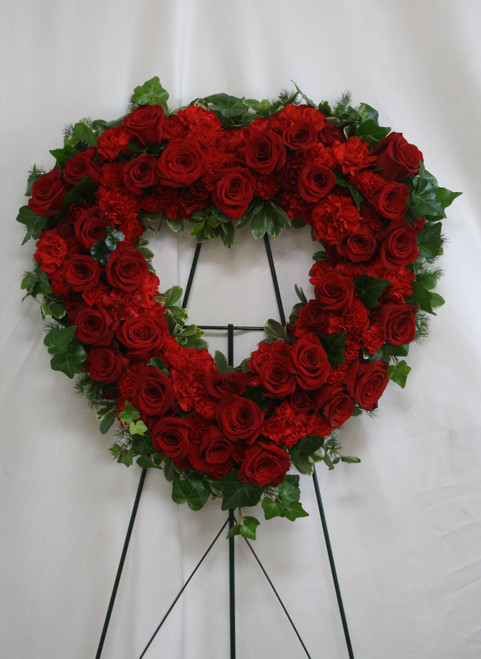 "Forever Blessed Red Rose Heart Tribute Spray by Enchanted Florist Pasadena TX. A vibrant red spray of red roses and red carnations designed into a heart shaped sympathy easel. One last spectacular remembrance for that special someone. Approximately 20""H x 20""W STANDARD (size does not include stand)   SKU RM550"