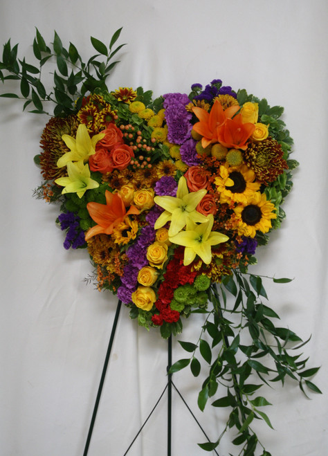 "Garden of Memories Yellow, Orange, and Purple Heart Wreath by Enchanted Florist Pasadena TX. A vibrant patchwork of beautiful flowers including orange and yellow asiatic lilies, yellow sunflowers, orange and yellow roses, bells of ireland, green and yellow buttons, bronze mums, orange hypericum all arranged on a solid heart shaped wreath. Approximately 26""H x 20""W (size does not include stand)   SKU RM551"