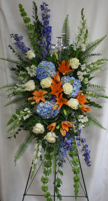 """Blue Orange and White Large Crystal Cross Standing Spray from Enchanted Florist.  This special spray includes blue hydrangea, white roses, orange oriental lilies, white alstroemeria, bells of Ireland, blue delphinium, white snapdragons, eucalyptus, and and assorted greenery foliages. Delivered on a wire easel with a Large Crystal Cross Keepsake. Standing spray is approximately 29"""" W x 49"""" H (Size does not include easel) SKU RM555"""