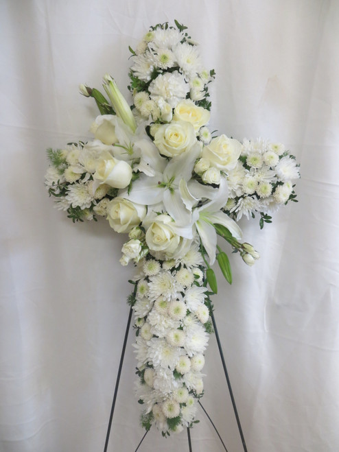"""Angelic All White Funeral Cross of Flowers from Enchanted Florist. Stunning funeral flowers such as white roses, carnations, and lilies are arranged on this floral cross that is covered in white mums and button flowers is full of love and devotion, arriving on a wire funeral easel. Approximately 26"""" W x 36"""" H (Dimensions do not include easel) SKU RM579"""