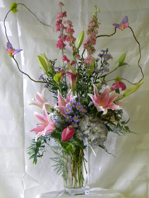 """Wild Butterflies Arrangement with Blue Hydrangeas from Enchanted Florist is a perfect mix of the best flowers spring has to offer. Mini calla lilies, hydrangeas, fragrant stargazer lilies, larkspur and of course the wild dancing butterflies. Arrives in a clear vase expertly designed by our floral designers. Approximately 36""""H x 12""""W. For local delivery only. SKU RM107"""