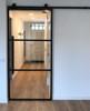 three panel glass metal barn door with no kick plate