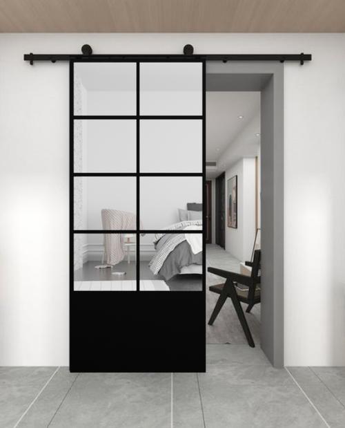The Vivian 8 Panel Mirror Sliding Barn Door With Kick Plate. Lifestyle image of bedroom door.