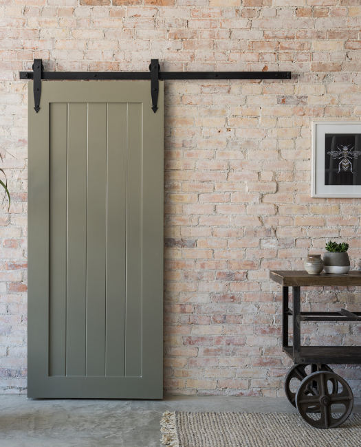 Hudson painted sage green vertical plank wood custom sliding barn door against brick wall in family room.