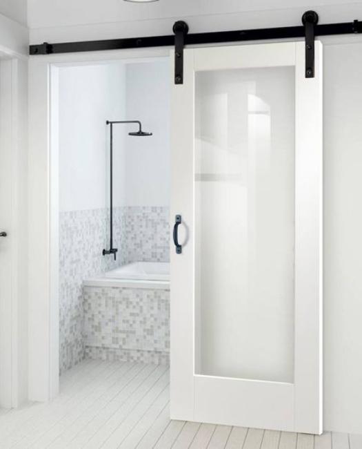 bathroom lifestyle of white wood frame full panel glass sliding barn door