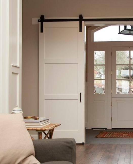 white 3 panel wood shaker custom sliding barn door in entry foyer to colonial home.