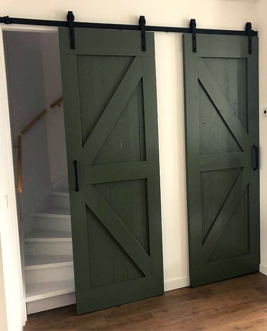 Dark Green sliding Sonoma Double Barn Door covering the curved stairscase and