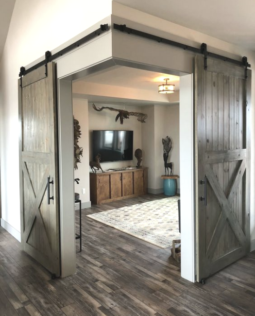 grey stained lake placid double barn doors used to separate a playroom from the family room. Sliding walls completing a corner. corner barn doors