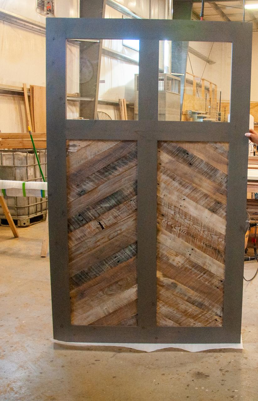 Reclaimed with a window Fully Custom Sliding Barn Door in workshop