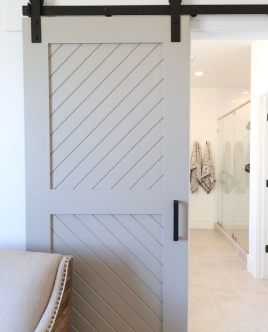 the Audrey cream two panel angle etched wood custom sliding barn door in master bedroom