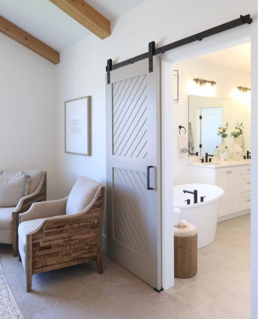 the Audrey cream two panel angle etched wood custom sliding barn door in master bedroom shot on an angle