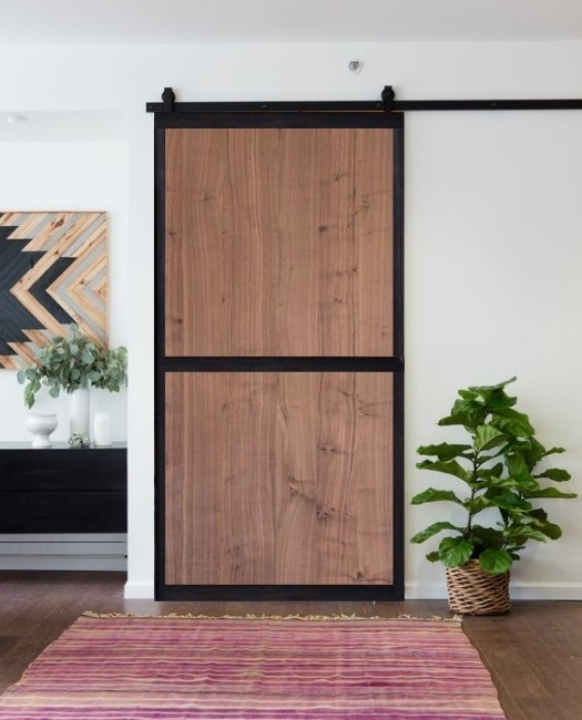 Walnut stained two panel wood jennie custom barn door with steel frame