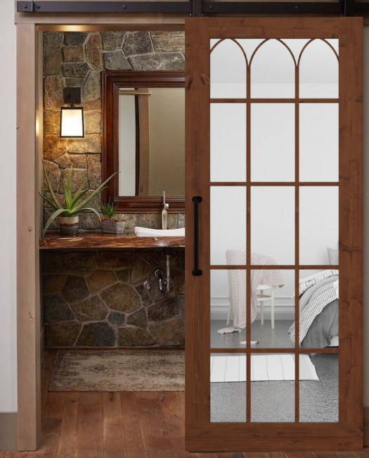 lifestyle of bedroom on suit sliding custom barn door with wood frame mirror and arched wood grid