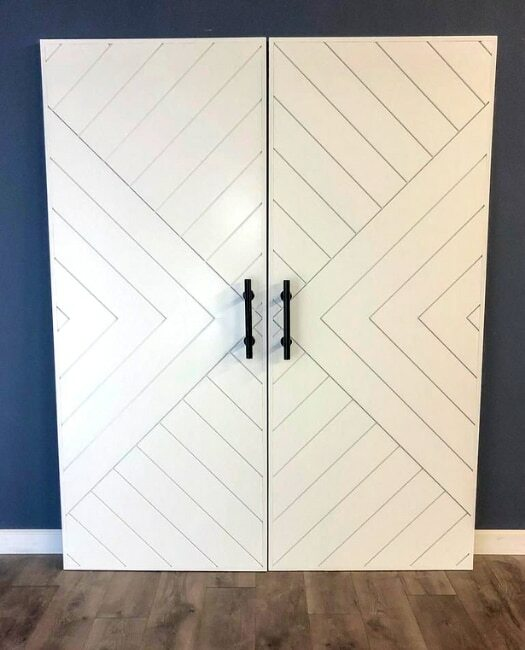 white painted modern arrow custom sliding barn door not installed in dining room against blue wall.