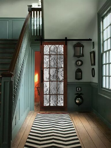 lifestyle of hallway sliding barn door wood frame arched wood grid and mercury mirrored glass