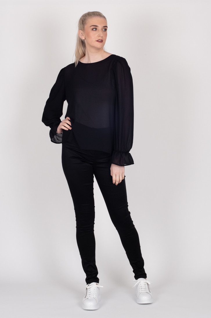 Tall model showcasing the black long sleeve Amelia top with frilly cuff and black pants