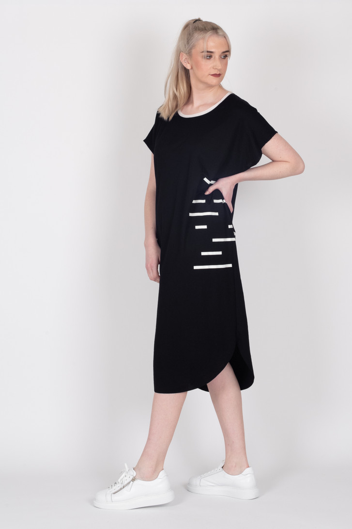 Tall model wearing Style X Lab brand Crossing the Lines dress in black with white stripes