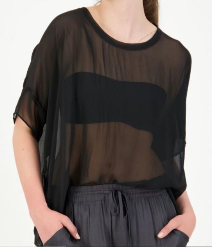 Woman modelling black sheer Breezy top for tall women worn tucked in over Storm satin pants