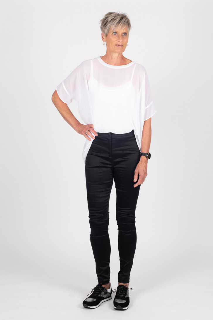 Woman wearing white Breezy top for tall women with Storm black satin tuxedo pants